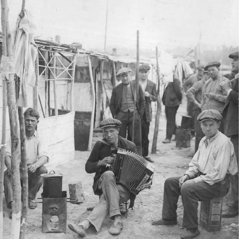 Homens sentados em frente a barracos em favela
