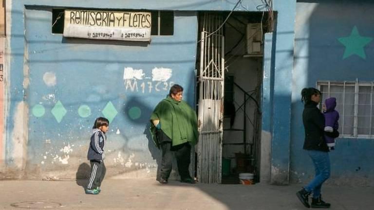 Mulher e criança caminham em frente à construção em favela