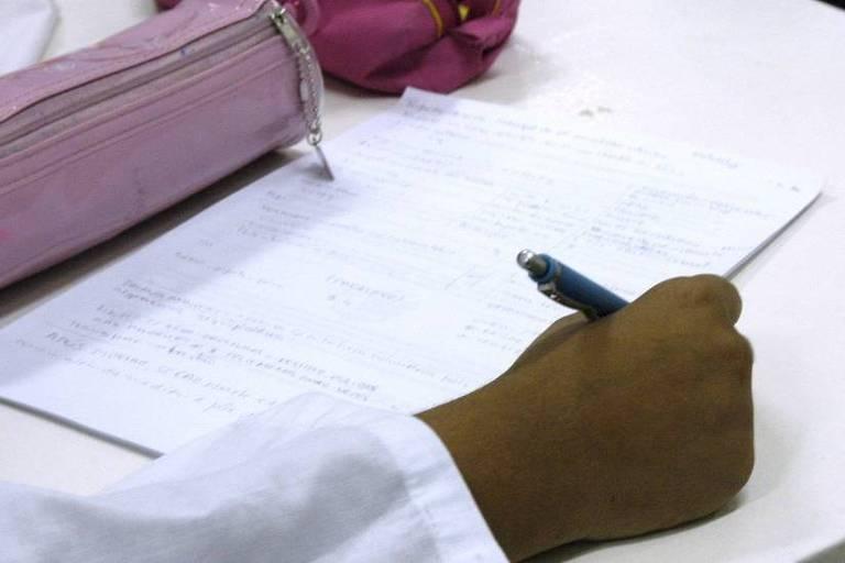 Pessoa escreve em papel