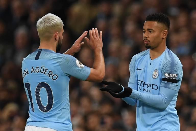 Agüero, à esquerda, cumprimenta Gabriel Jesus, seu colega no Manchester City. Eles vestem o uniforme azul do clube. Agüero leva a camisa dez.