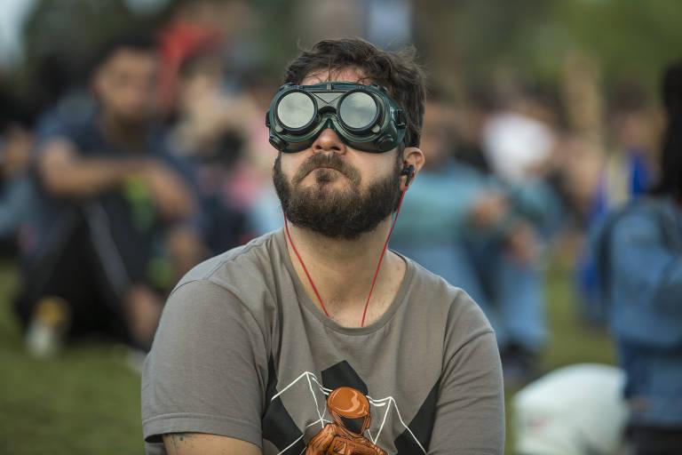 Homem, com óculos, na Praça Pôr do Sol, em Pinheiros, assiste eclipse solar