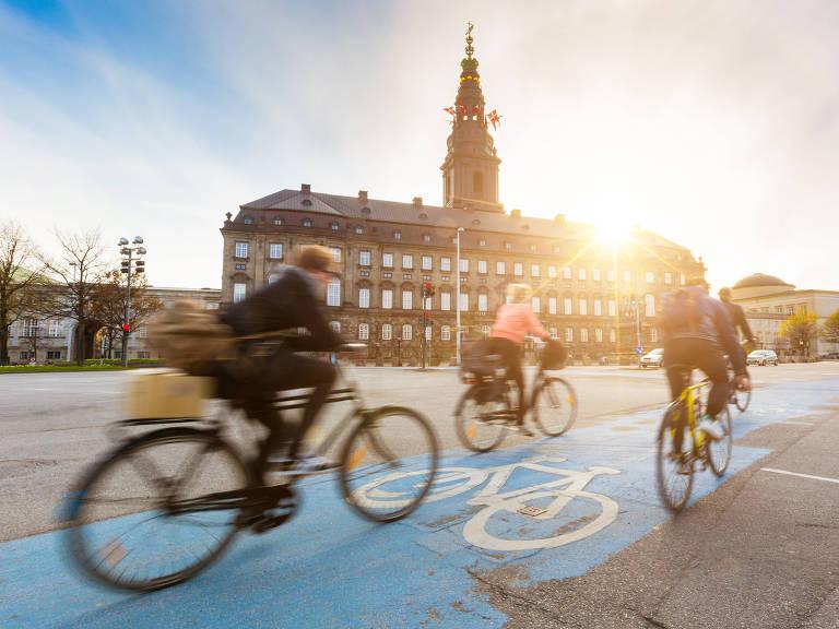 Um grupo de ciclistas passa em frente a um prédio com a luz do sol refletindo sobre eles