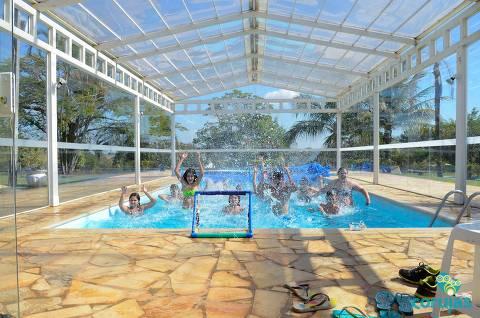 Participantes do acampamento Corujas brincam em piscina coberta