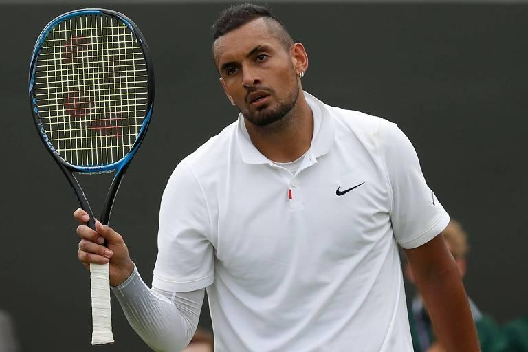 O tenista australiano Nick Kyrgios, com camiseta branca da marca Nike, mostra sua raquete durante partida em Wimbledon