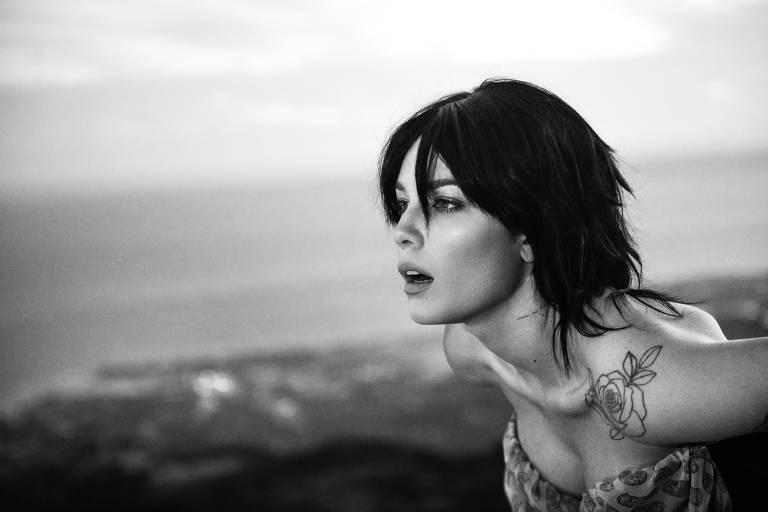 mulher de cabelo preto olhando para o horizonte