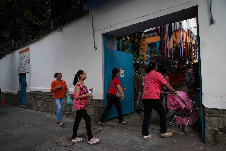 Pais entram com filhos em escola municipal; mãe carrega bebê em carrinho