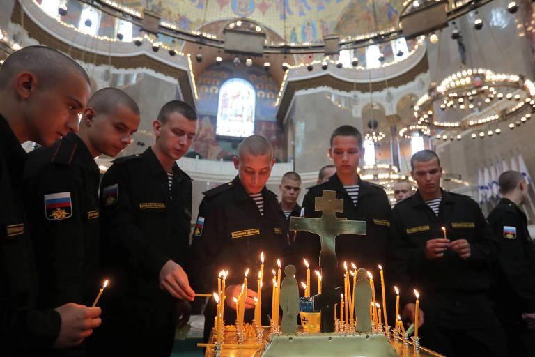 Marinheiros acendem velas em homenagem aos mortos no acidente, na Catedral Naval de Kronstadt, cidade russa