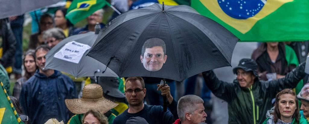 guarda-chuva com cara de moro em meio a protesto