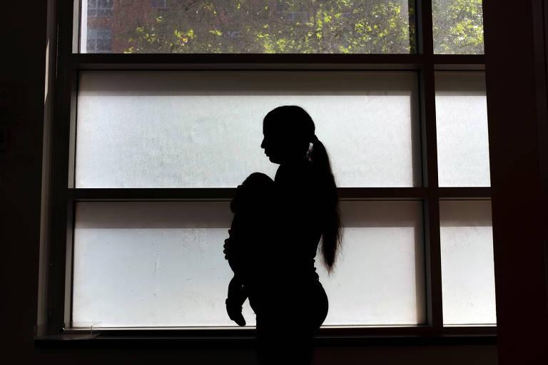 Silheta na contra-luz de mulher que carrega bebê no colo