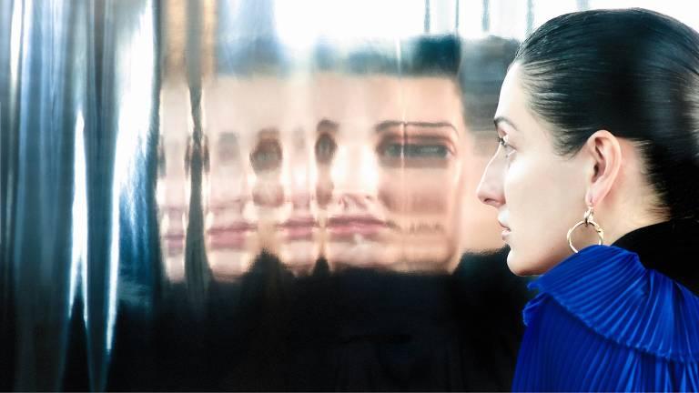mulher com cabelo preso olhando vários reflexos seus em um espelho