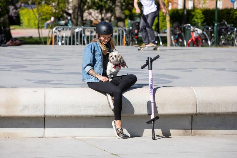 Mulher com cachorro em praça, próxima a um pula-pula rosa