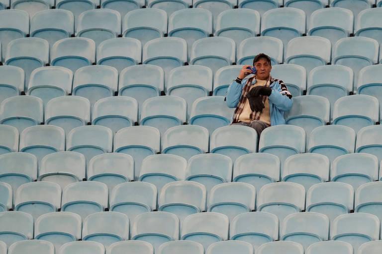 Torcedor solitário, rodeado de cadeiras vazias, na Arena do Grêmio antes de jogo entre Chile e Peru, pela semifinal