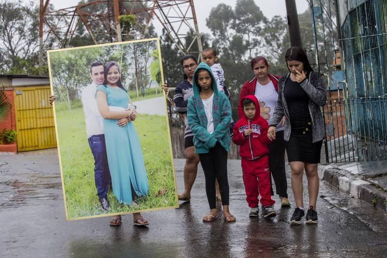 Quatro mulheres e duas crianças posam ao lado de um cartaz grande com uma foto do cabeleireiro abraçado a uma mulher