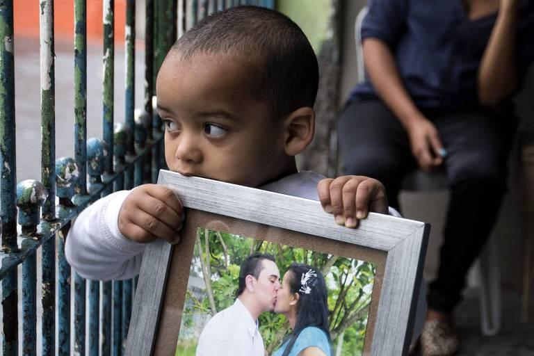 Bebê segura porta-retrato perto do rosto, com uma foto de Sidney e a ex-mulher se beijando