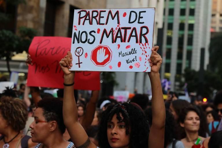 """Mulher ergue cartaz com a frase """"Parem de nos matar"""" em meio a multidão na avenida Paulista"""