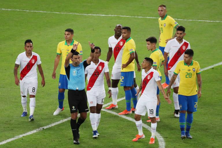 Jogadores das duas seleções observam árbitro fazer o sinal de consulta ao VAR