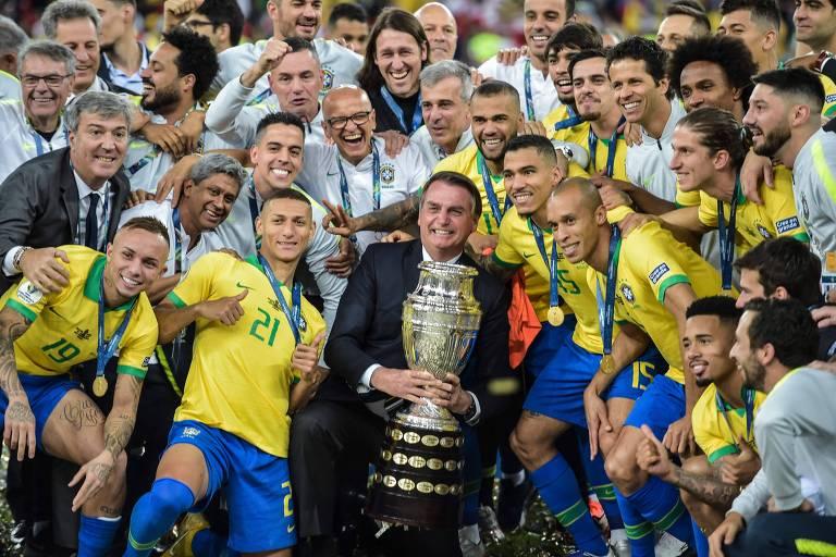Bolsonaro posa para foto com a taça da Copa América, em meio aos jogadores da seleção brasileira