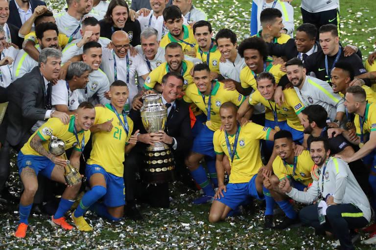 Bolsonaro posa para foto com o troféu da Copa América e rodeado por jogadores e comissão técnica da seleção brasileira