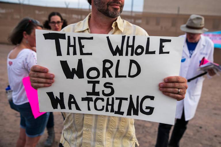 """manifestante segura cartaz em que se lê """"o mundo está de olho"""""""