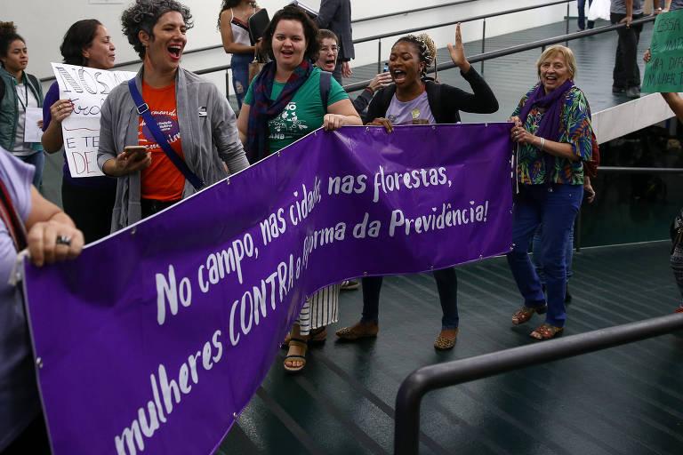 """Em uma rampa do Congresso, mulheres seguram faixa roxa na qual está escrito em branco """"no campo, na cidade  ou na floresta, mulheres contra a reforma da Previdência"""""""