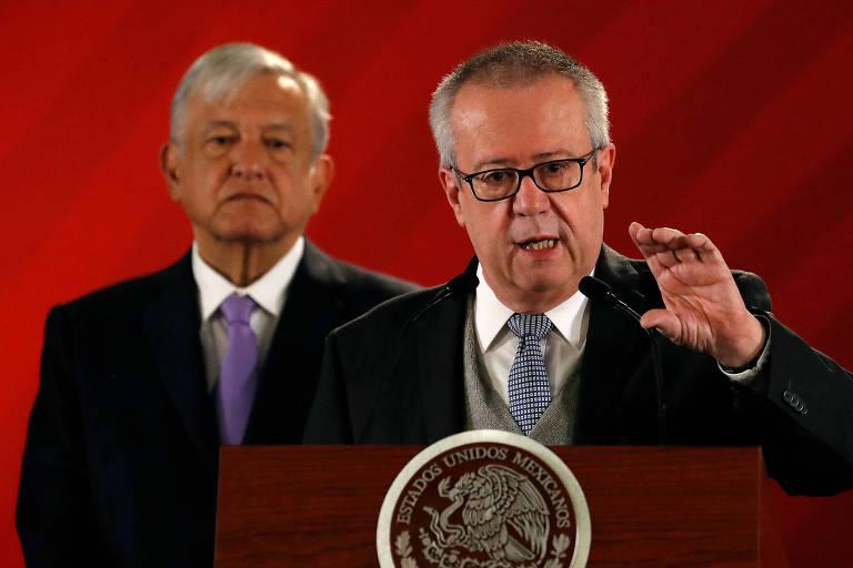Carlos Urzúa, então Ministro da Fazenda do México, durante entrevista coletiva; atrás dele, o presidente Andrés Manuel López Obrador