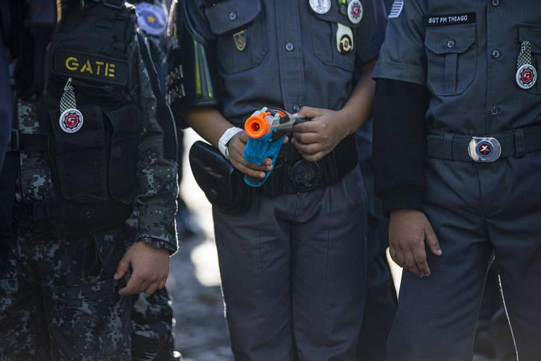Crianças desfilam com simulacros de armas no 9 de julho