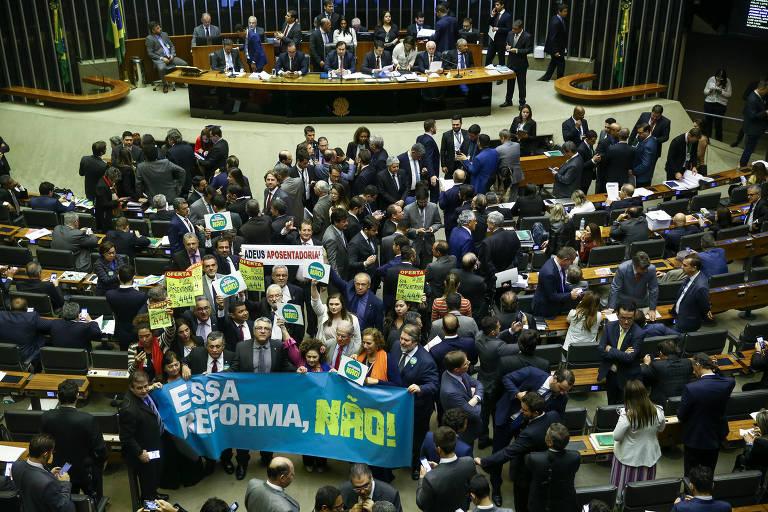 No plenário da Câmara, deputados da oposição erguem faixas e cartazes contra a reforma da Previdência