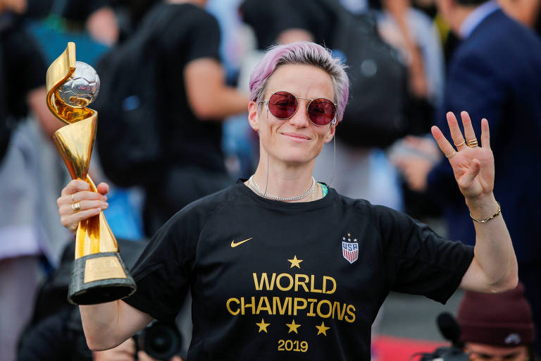 Rapinoe segura o troféu da Copa do Mundo na chegada da equipe ao Aeroporto Internacional de Newark, em Nova Jersey