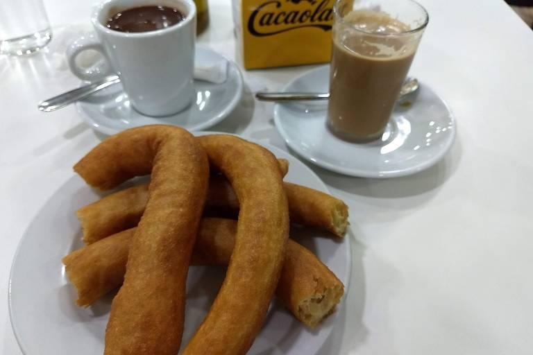 Prato com churros, caneca de chocolate e copo com café
