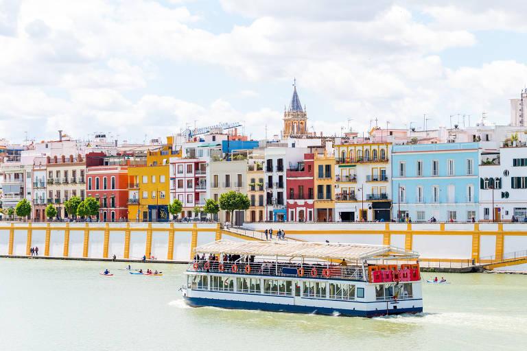 Barco navega em rio, com casas coloridas ao fundo