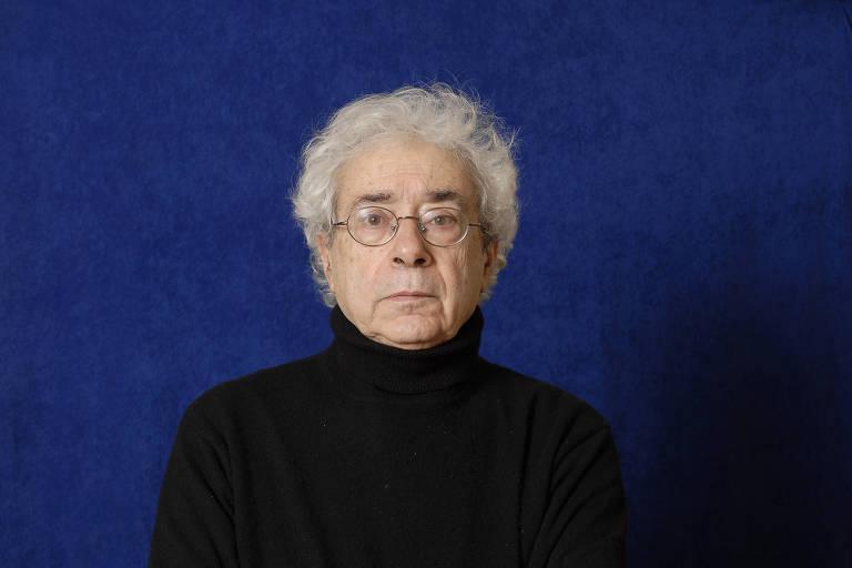 O sociólogo francês Luc Boltanski, com blusa preta de gola, em fundo azul