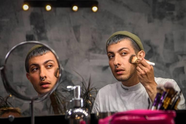 O blogger de beleza Gevorg, 26, passa maquiagem em frente à espelho em um salão de beleza em Moscou; ele usa um pincel para aplicar pó na sua buchecha direita