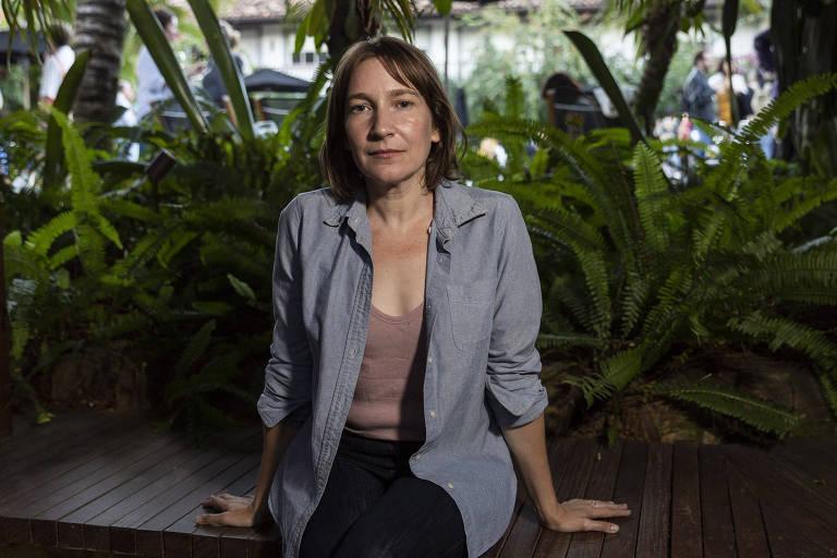 A escritora canadense Sheila Heti, autora de 'Maternidade', sentada com as mãos apoiadas em banco; ao fundo, plantas do jardim