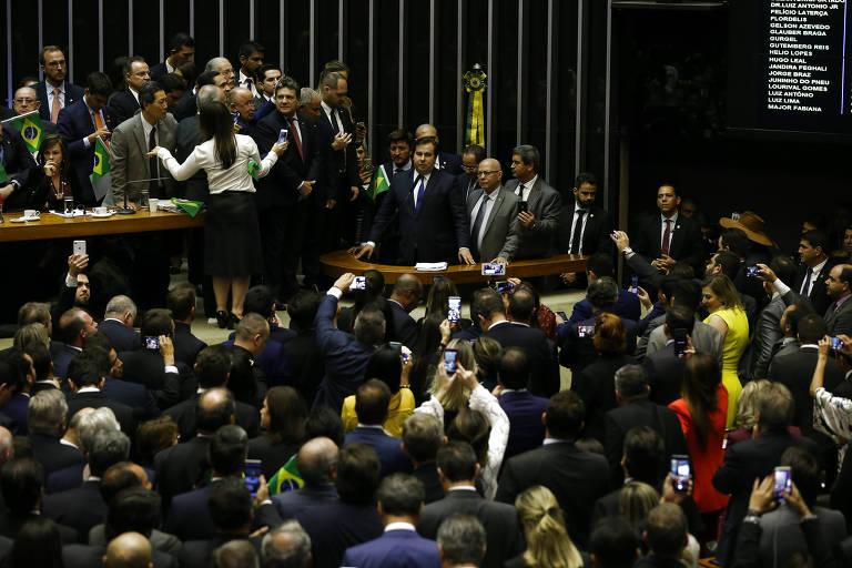 Maia discursa, cercado por deputados