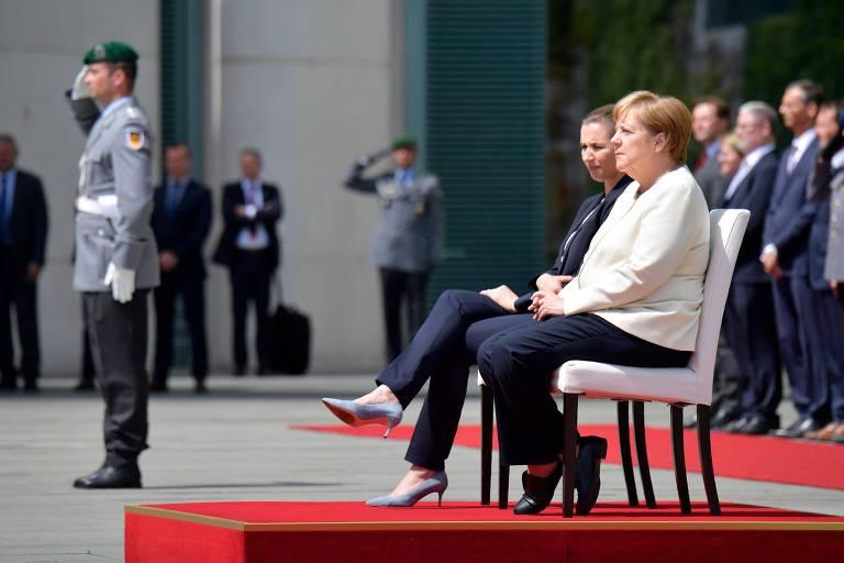 A chanceler alemã, Angela Merkal, e a primeira-ministra da Dinamarca, Mette Frederiksen, ouvem os respectivos hinos nacionais sentadas em solenidade em Berlim