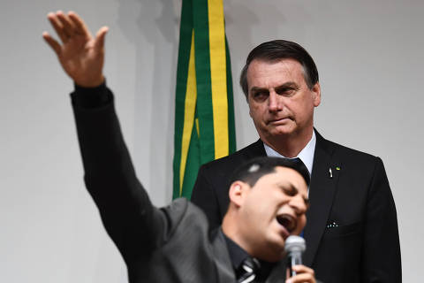 Brazilian President Jair Bolsonaro (behind) listens as an evangelical pastor speaks before deputies vote a pension reform bill at the National Congress in Brasilia, on July 10, 2019. - After several delays and amendments, pro-government deputies are working to get the necessary approval to pass a pension reform bill to the Senate before the Congress's mid-year recess. (Photo by EVARISTO SA / AFP) ORG XMIT: ESA630