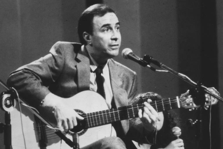 João Gilberto sentado com violão e microfone