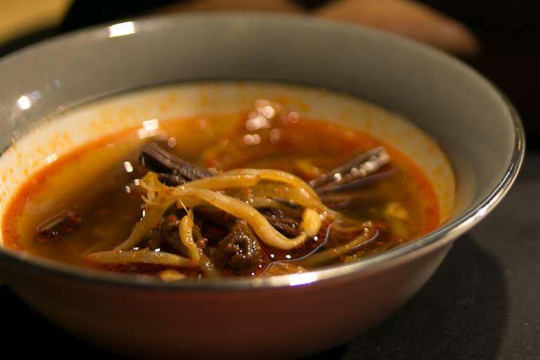 """Chef Paulo Shin, do Komah, prepara sopa de base bovina com broto de samambaia e de feijão na Peixaria Mitsugi; receita é inspirada no anime """"O Reino dos Gatos"""""""