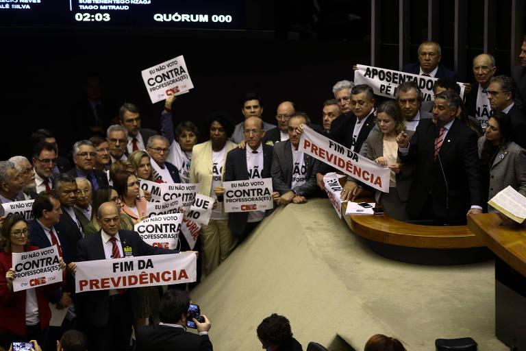 Deputados da oposição erguem cartazes contra a reforma na quarta-feira (10)