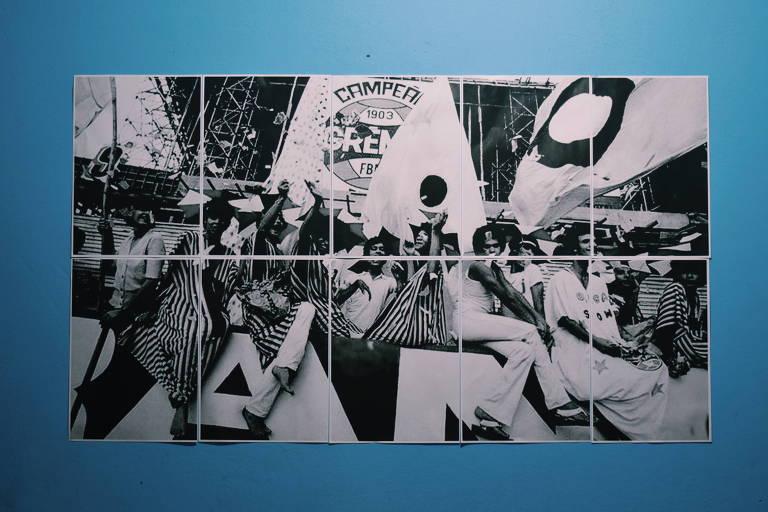 Painel fotográfico que mostra a torcida Coligay em ação no estádio com bandeiras