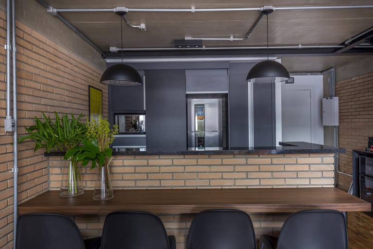 No projeto deste loft, a arquiteta Carina Korman optou por uma bancada mais alta que a pia e a mesa; assim, quem está sentado não consegue ver a louça suja do outro lado