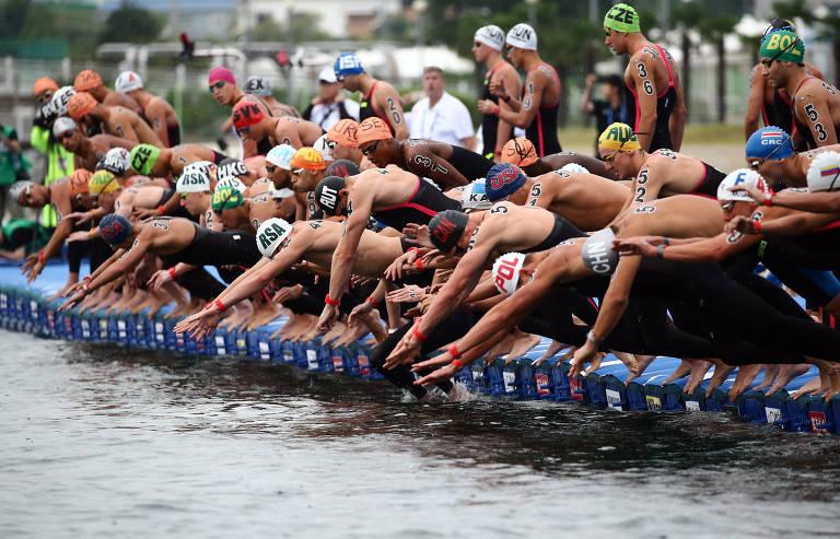 vários homens, sem camisa e com touca, pulam na água