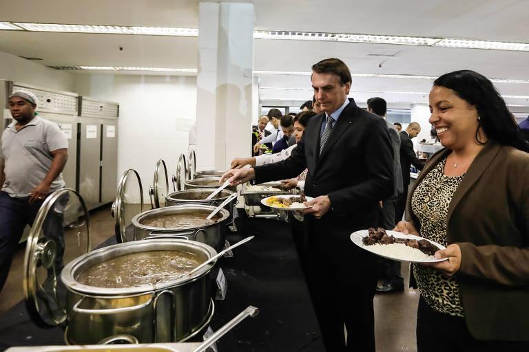 bolsonaro se serve em meio a panelões de comida