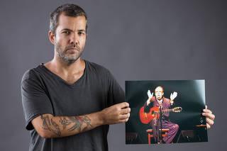 O fotógrafo João Wainer posa com foto de João Gilberto