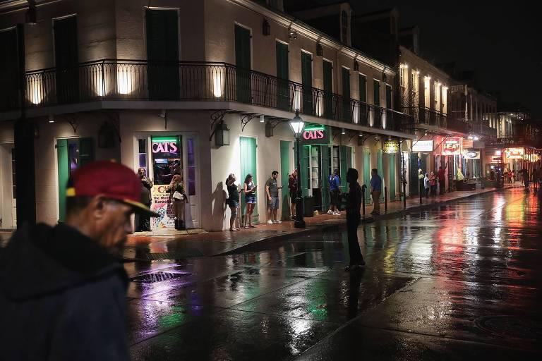 Moradores de Nova Orleans circulam pela cidade na madrugada deste sábado (13) apesar de alerta para chuva forte