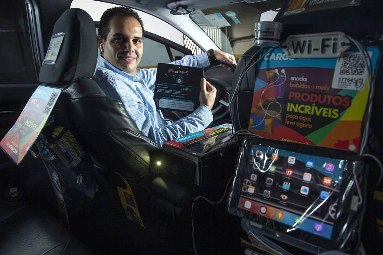 homem de camisa sentado ao volante de um carro no qual há anúncios de produtos