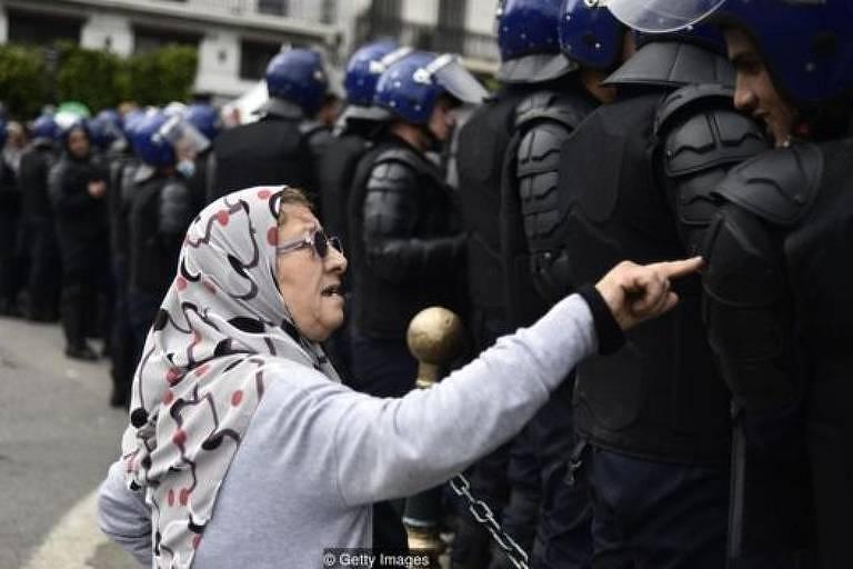Uma senhora conversa com membros das forças de segurança durante os recentes protestos contra o governo na Argélia
