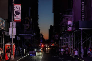 Dark buildings along a dark street are seen near Times Square area, as a blackout affects buildings and traffic during widespread power outages in the Manhattan borough of New York