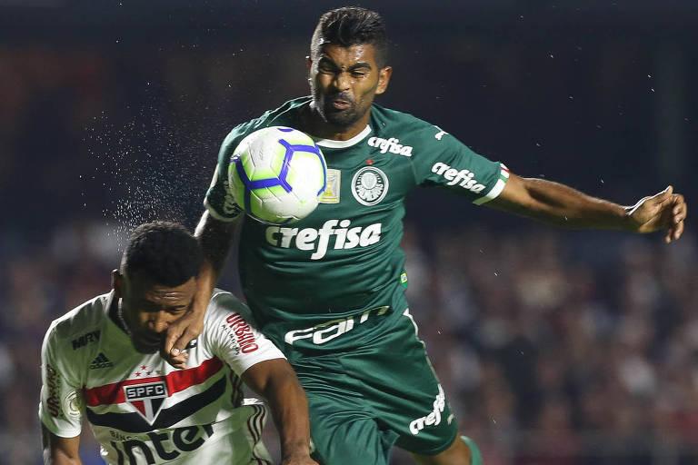 O palmeirense Thiago Santos disputa a bola com o são-paulino Luan