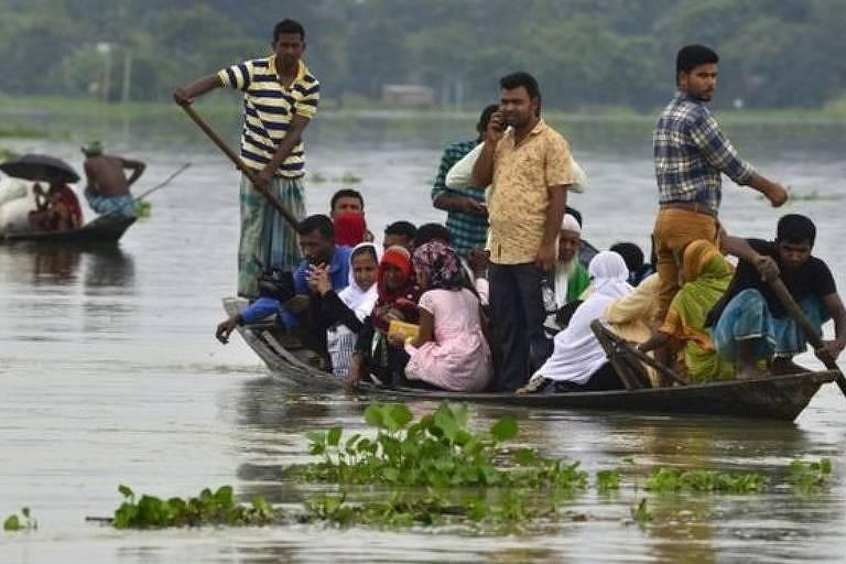 Homens e mulheres em barco em meio a inundação